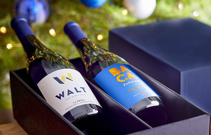 Visit WALT BACA Healdsburg imagery showing a bottle of WALt Pinot Noir and BACA Zinfandel in a holiday gift box.